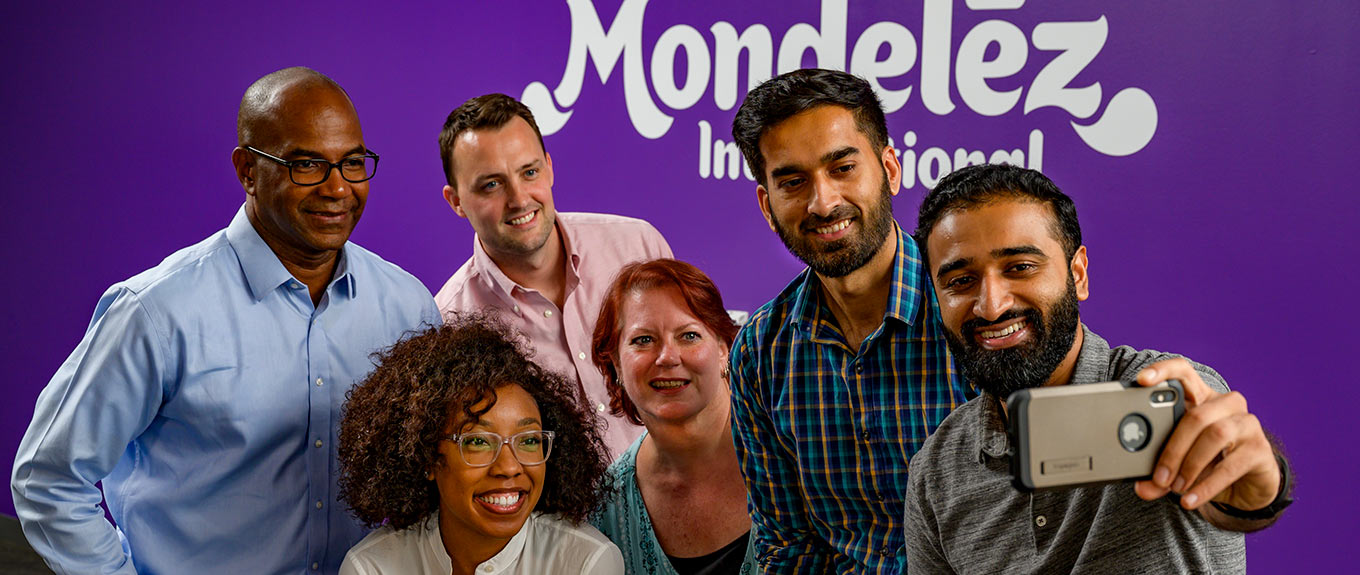 3 multicultural Mondelez staff sitting around a laptop smiling and talking.