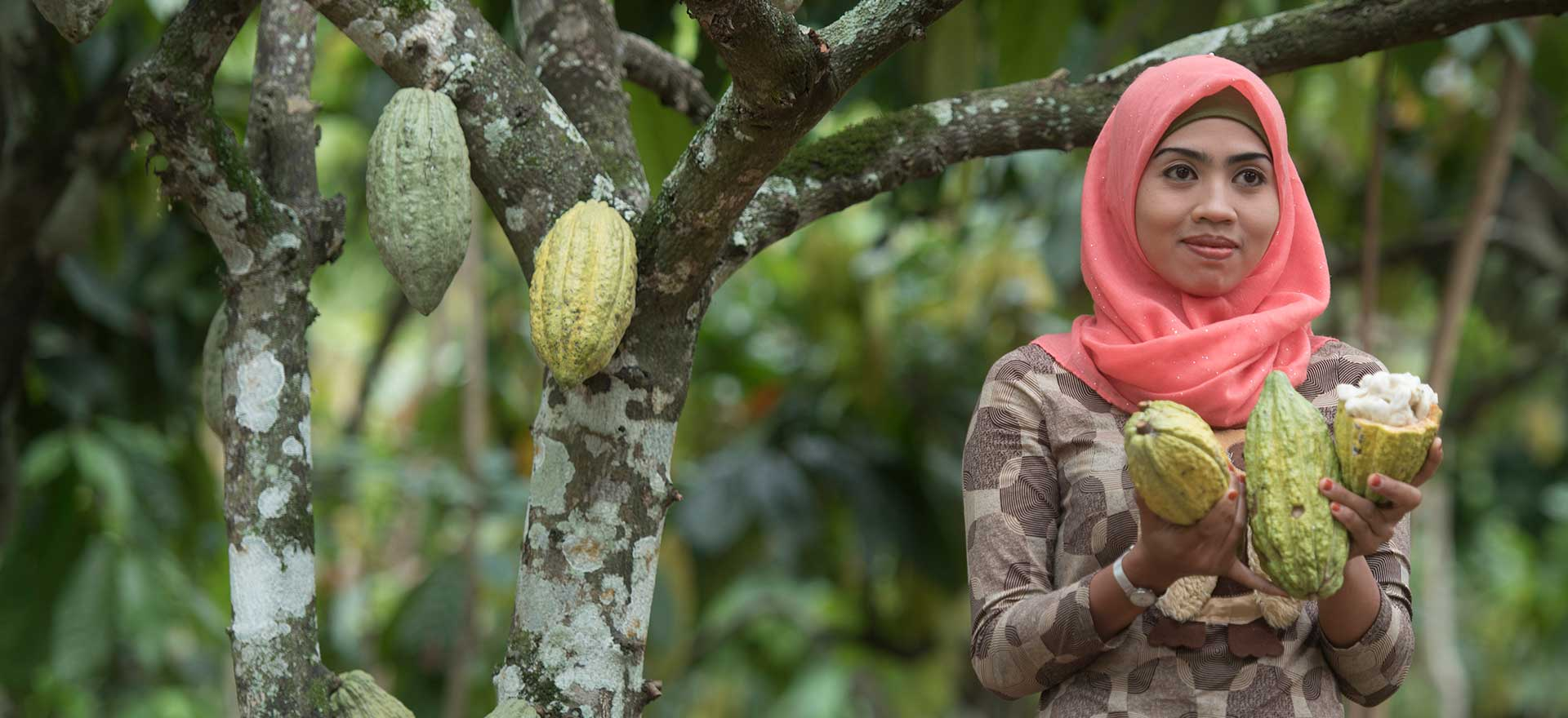 Indonesian woman smiling while standing next to a tree and holding fruits that have been picked from the tree.