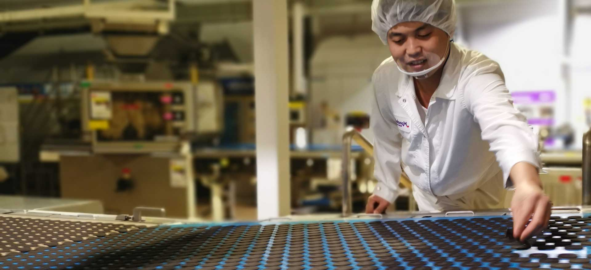 Mondelez factory worker smiling while inspecting Oreo cookies on assembly line.