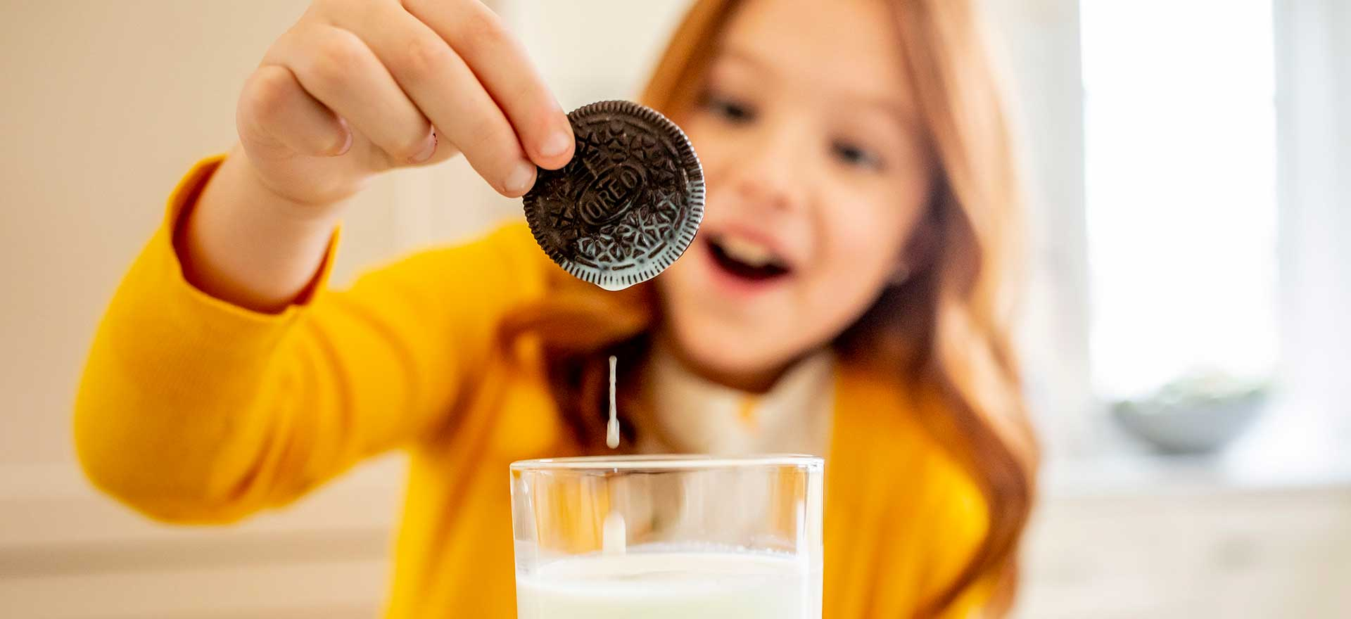 Young girl excitedly dunking an Oreo cookie into milk.