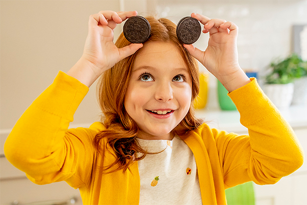 Girl holding Oreo cookies over head smiling