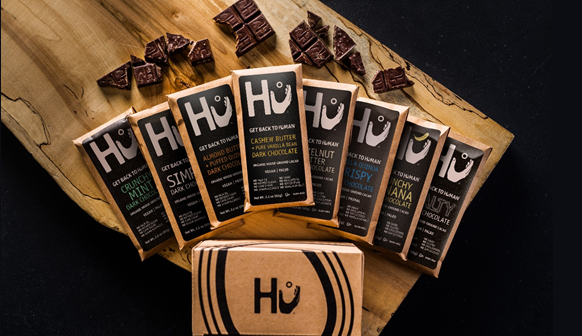 Overhead shot of 8 different flavours of Hu bars on a woodgrain table with various bits and pieces of individuals chocolate squares strewn about.