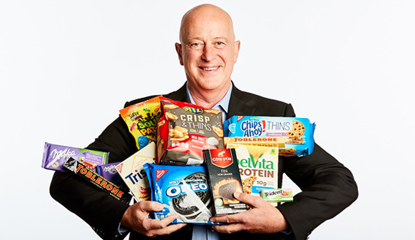 Mondelēz CEO Dirk Van de Put holding a wide range of Mondelez products in his hands while he smiles.