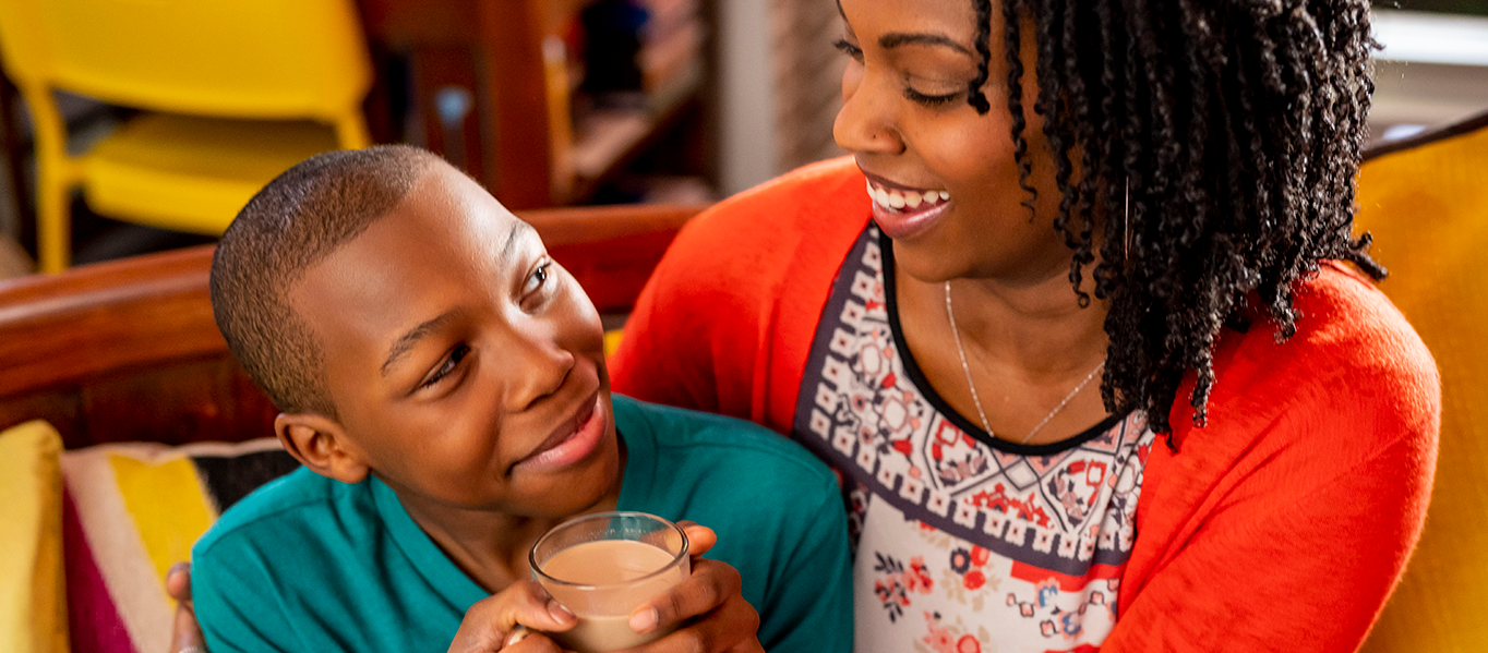 Mother and son smiling at each other while son drinks from a glass of Chocolate milk.