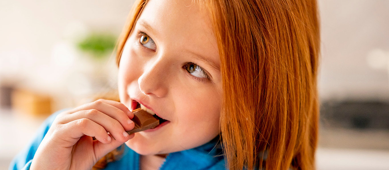 Little girl smiling while she eats a chocolate snack.