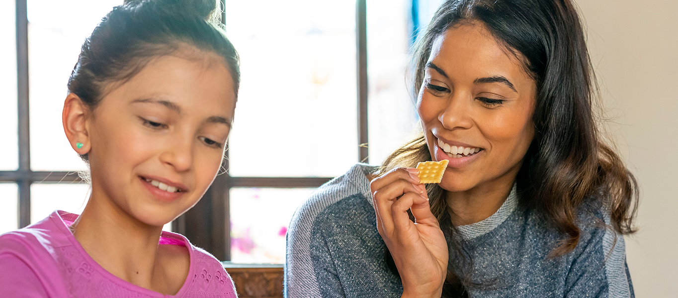 Mother and daughter eating a cracker and smiling.