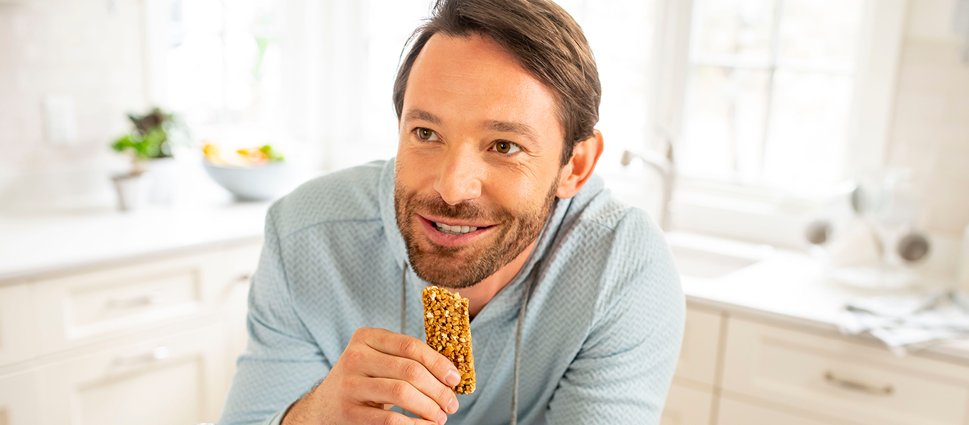 Man leaning over counter and smiling while eating a granola snack.
