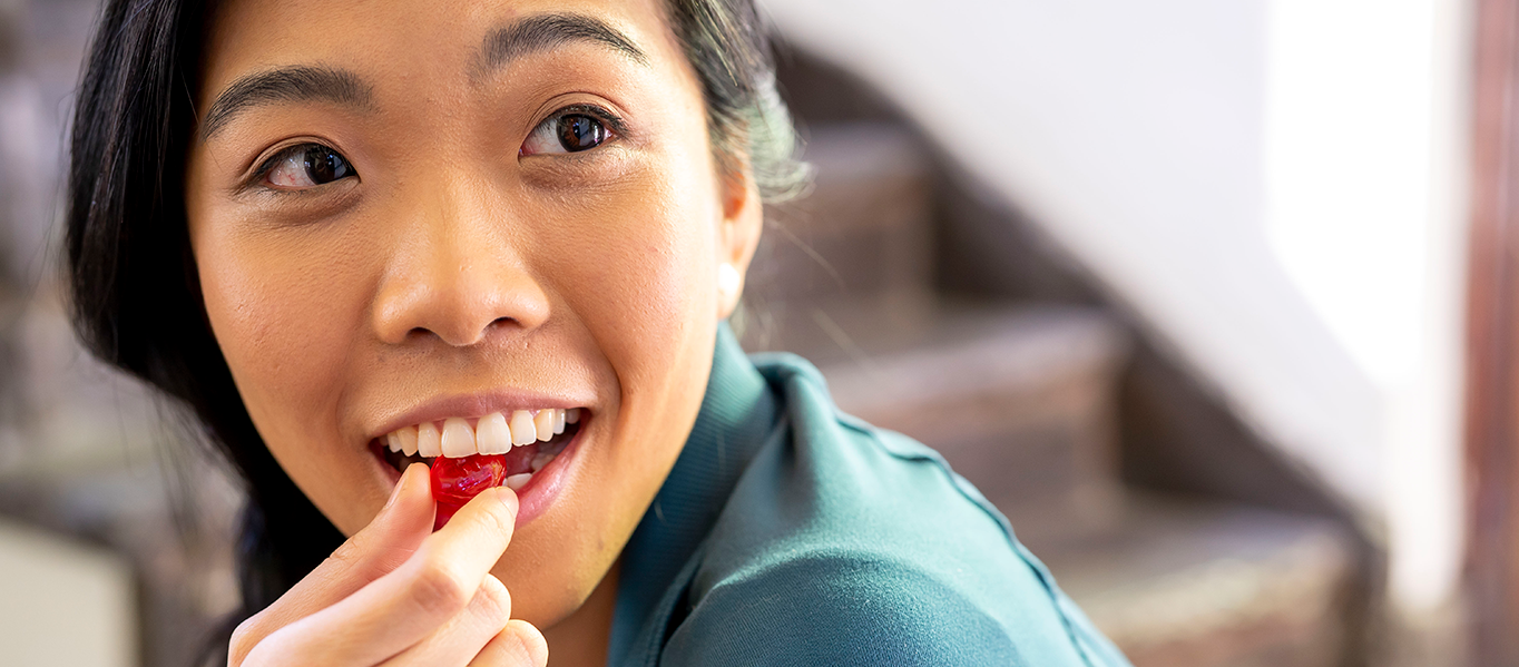 Asian woman eating a halls candy and smiling.