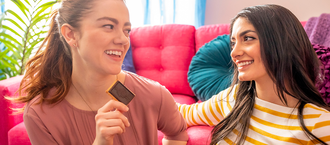 2 women smiling at each other while 1 eats a chocolate biscuit.