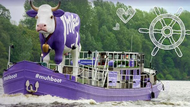 Purple milka boat with giant purple cow on it.