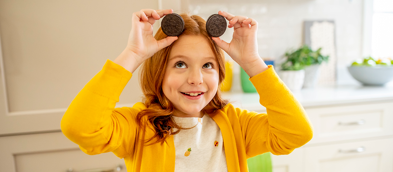 Little girl holding 2 Oreo cookies above her head to form mouse ears while she smiles.