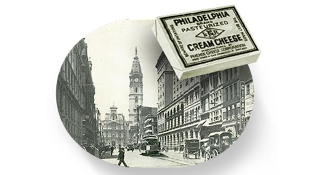 Picture from 1880 of Philadelphia and a package of Philadelphia cream cheese in the foreground also from that time.