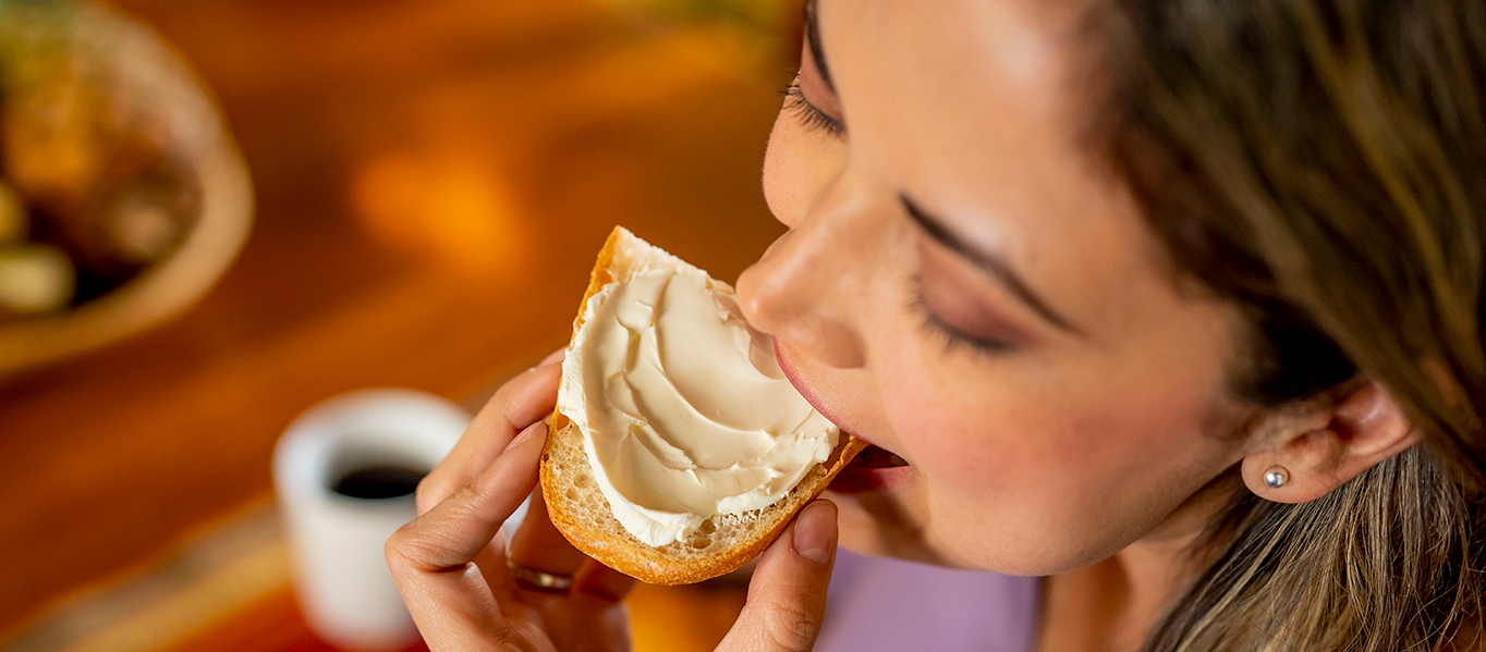 Woman smiling while eating toast with Philadelphia cream cheese spread on it.