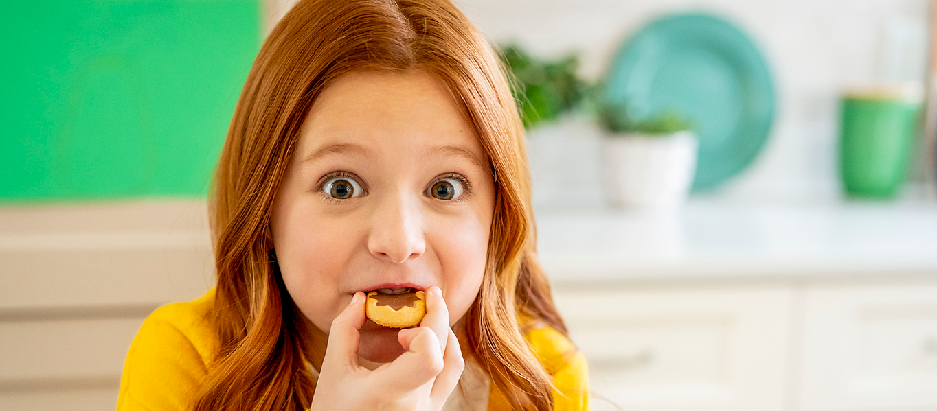 Young girl with a surprised but happy look on her face while she eats a Prince snack.
