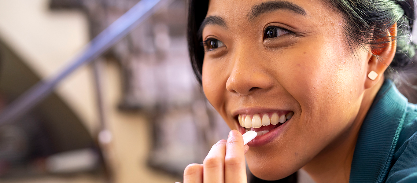 Asian woman smiles while she puts a stride gum piece into her mouth.