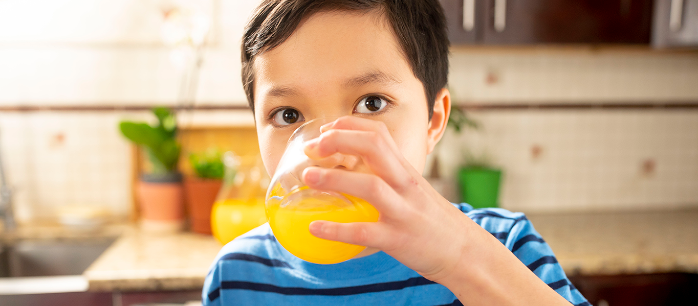 Boy drinks from a glass of orange tang.