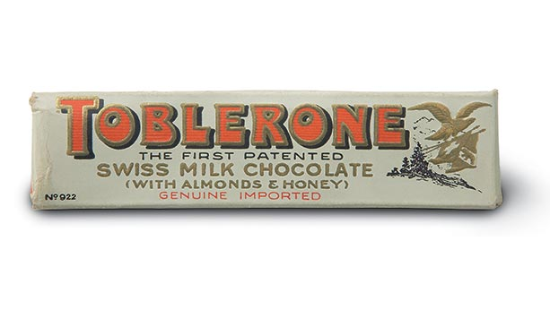 1908 packaging of first Toblerone package. White colour scheme with red Toblerone lettering. Swiss milk chocolate with almonds and honey flavour.