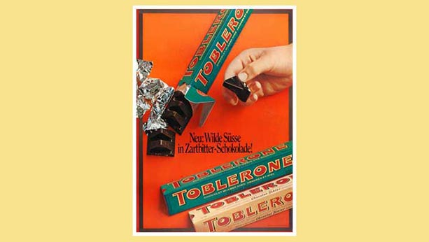 Ad from 1969 of Dark chocolate Toblerone. 2 packets of dark chocolate Toblerone - 1 open with a hand holding a piece from that package. 1 original flavour package unopened.