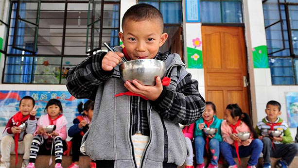 Asian children at a school sit down eating bowls of food while 1 stands in the foreground also eating from a bowl and smiling.