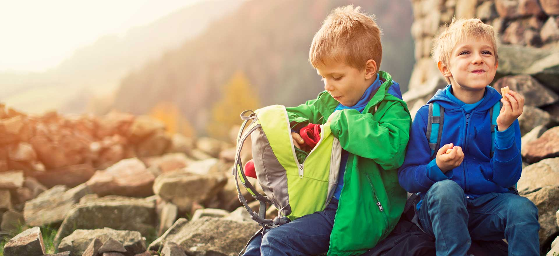 2 boys sitting on a mountain side. 1 is smiling and eating a snack while the other rummages through his backpack.