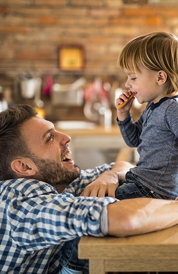 Father leaning on table as he smiles at his son who is sitting in front of him. Child is also smiling while eating a cookie.